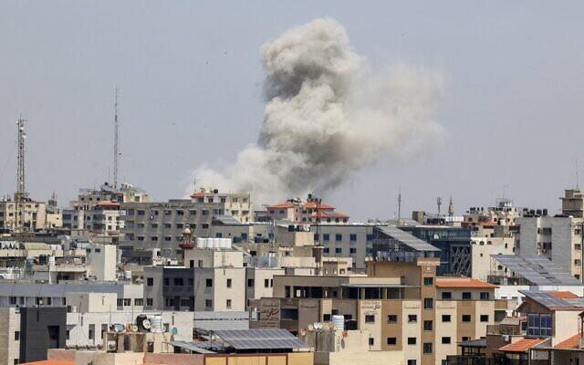 Bola api menimbulkan gumpalan asap dari sebuah bangunan di distrik pemukiman Rimal, Kota Gaza, pada Kamis 20 Mei 2021, saat Israel menyerang daerah kantong/enclave yang dikendalikan Hamas sebagai tanggapan atas tembakan roket dari kelompok milisi tersebut. (MAHMUD HAMS / AFP via Times of Israel)