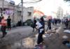 Orang-orang berjalan melewati puing-puing di jalan di lokasi serangan udara Israel, di Kota Gaza pada Mei [Mohammed Salem / Reuters via Al Jazeera)]