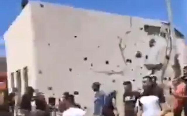 Warga Palestina memeriksa kerusakan yang terjadi pada sebuah bangunan di kota Azzun, Tepi Barat, setelah sebuah roket yang ditembakkan dari Jalur Gaza menabrak di dekatnya, pada 15 Mei 2021 (Tangkapan layar: Twitter)