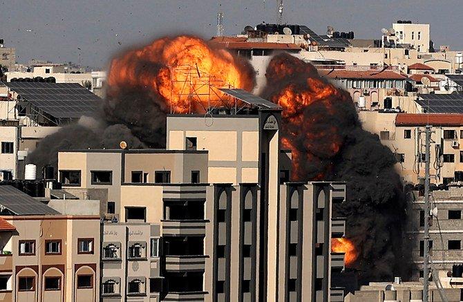 Ledakan yang terjadi saat serangan Israel menargetkan sebuah bangunan di Kota Gaza pada Jumat 14 Mei 2021. Israel menggempur Gaza dan mengerahkan pasukan tambahan ke perbatasan saat Palestina menembakkan rentetan roket ke belakang. (AFP via Arab News)