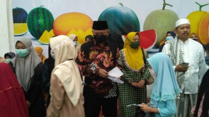 H Slamet Sulistiyono saat membagikan zakat mal kepada mustahik (anak yatim) di aula PT BCA, Jumat (7/5). (Foto: NU Online/Aryudi A Razaq)