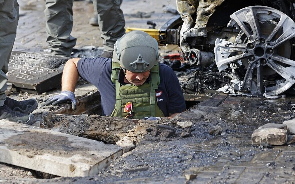 Seorang anggota pasukan keamanan Israel memeriksa sebuah kawah di kota Ashkelon di Israel selatan menyusul serangan roket yang ditembakkan dari Jalur Gaza, pada 16 Mei 2021. (JACK GUEZ / AFP)