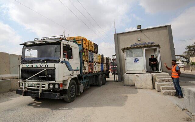 Foto Ilustrasi. Seorang polisi Palestina melambai di atas truk saat masuk melalui Kerem Shalom yang menyeberang ke Jalur Gaza pada 1 September 2020, setelah kesepakatan yang dimediasi oleh Qatar dengan Israel. (KATA KHATIB / AFP via Times of Israel)