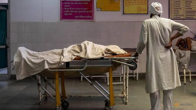 Seorang pria berdiri di samping tubuh istrinya, yang meninggal karena sesak napas, di dalam bangsal darurat rumah sakit yang dikelola pemerintah, di tengah pandemi penyakit coronavirus (COVID-19), di Bijnor, Uttar Pradesh, India, 11 Mei. , 2021. REUTERS / Denmark Siddiqui