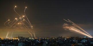 Roket (l) terlihat di langit malam ditembakkan ke arah Israel dari Beit Lahia di Jalur Gaza utara pada 14 Mei 2021, sementara pencegat Iron Dome naik untuk menghancurkannya. (Foto oleh ANAS BABA / AFP)