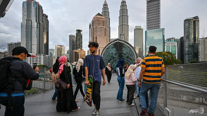 Orang-orang berjalan dan berfoto di sepanjang Saloma Link Bridge di Kuala Lumpur pada 19 Desember 2020. (Foto: AFP/Mohd RASFAN via CNA)