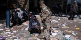 Seorang tersangka penjarah memohon kepada seorang tentara Pasukan Pertahanan Nasional Afrika Selatan (SANDF) yang menangkap tersangka penjarah di mal Jabulani di Soweto di pinggiran Johannesburg pada 13 Juli 2021 [Emmanuel Croset/AFP/Al Jazeera]