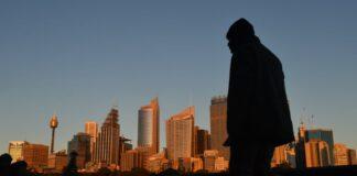 Seorang pria berjalan melewati cakrawala kota saat fajar di Sydney, Australia, di mana pasukan polisi dan tentara akan berpatroli di jalan-jalan untuk menegakkan pembatasan untuk menekan penularan Covid-19. (Foto: Mick Tsikas/AAP via Guardian)
