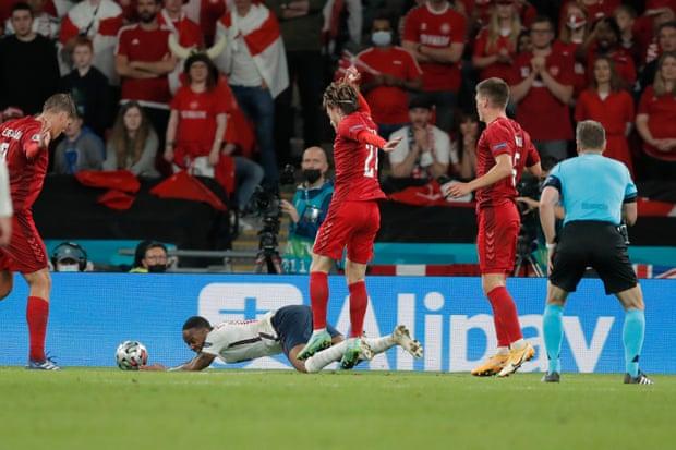 Raheem Sterling terjatuh oleh pelanggaran Joakim Mæhle pada semi final EURO 2020 antara Inggris v Denmark. Komite wasit UEFA tegaskan keputusan penalti untuk Inggris sudah benar. (Guardian)