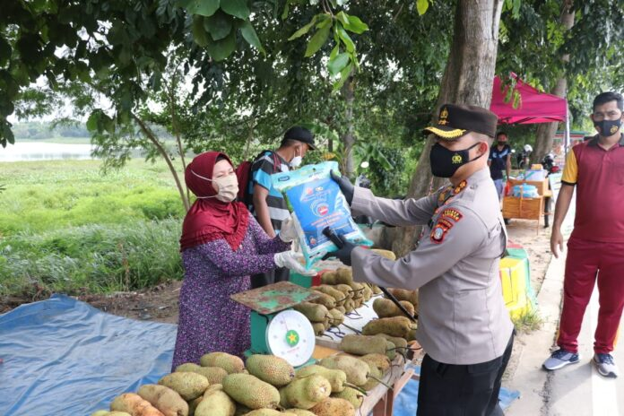 Kapolres Karimun AKBP Muhammad Adenan menyerahkan bantuan paket sembako kepada seorang pedagang buah di tepi jalan, Jumat (16/7/2021). Foto Suryakepri.com/YAHYA