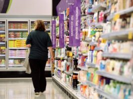 Seorang wanita berjalan melalui lorong gondola di cabang supermarket Australia, Woolworths. (Foto: Dan Peled/AAP viar Guardian)