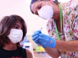 Seorang perawat di Wilmington, California, AS, memberikan penjelasan tentang vaksin Covid kepada warga yang akan divaksinasi. (Foto: Mario Tama/Getty Images via Guardian)