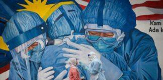 Seorang dokter klinik mengumpulkan sampel untuk pengujian virus corona dari seorang wanita di fasilitas skrining COVID-19 di Klinik Ajwa dekat mural yang menggambarkan garis depan medis di Shah Alam, negara bagian Selangor, Malaysia, pada Sabtu, 12 Desember 2020. (Foto: AP/Vincent Thian/CNA)