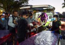 Relawan dan staf medis membawa seorang pria yang terluka untuk perawatan setelah dua ledakan kuat di Bandara Internasional Hamid Karzai, Kabul, Afghanistan, Kamis (28/8/2021). [Wakil Kohsar/AFP]