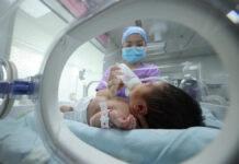 Seorang anggota staf medis memberi makan bayi di sebuah rumah sakit di Danzhai, di provinsi Guizhou barat daya China pada 11 Mei 2021. (Foto: STR/AFP/Getty Images via msn.com)