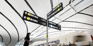 Seorang penumpang mendorong barang bawaannya ke area check-in di Bandara Internasional Daxing Beijing pada 12 Juli 2021, karena ratusan penerbangan dibatalkan di ibu kota. Foto: AFP / Wang Zhao