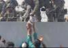 Gambar ini tersedia untuk AFP pada 20 Agustus menunjukkan seorang Marinir AS meraih seorang bayi di atas pagar ... [+] (COURTESY OF OMAR HAIDIRI/AFP VIA GETTY IMAGES - Forbes)