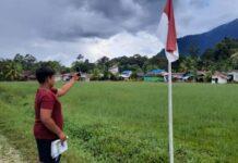 Foto Dino mencoba mencari sinyal internet di kaki bukit untuk mengerjakan soal dari sekolahnya. (Edho Sinaga/CNN Indonesia)