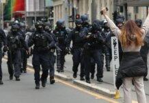 Seorang pengunjuk rasa sendirian menantang polisi anti huru hara ketika pekerja konstruksi dan demonstran berbaris di jalan-jalan menentang peraturan COVID-19 di Melbourne pada 22 September 2021. (Foto: AFP/Con Chronis via CNA)
