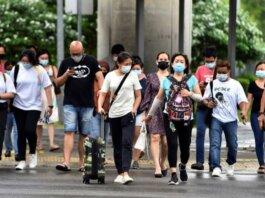 Para pejalan kakiyang mengenakan masker menyeberang jalan di tengah wabah Covid-19 di Singapura pada 14 Mei 2021. (Foto: Reuters/Caroline Chia via CNA)