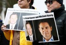 Orang-orang memegang plakat yang menyerukan China untuk membebaskan Michael Spavor dan Michael Kovrig di Mahkamah Agung BC di Vancouver pada 6 Maret 2019. (Foto: Reuters via Strats Times)