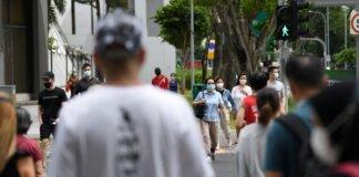 Pejalan kaki bermasker menyeberang jalan di Singapura. Kasus Covid-19 di Singapura sedang melonjak, mayoritas kasus lokal dan berada dalam komunitas. (Foto: Channel News Asia/Calvin Oh)