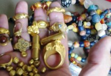 Segenggam harta karun berupa cincin emas, manik-manik dan koin emas cendana Sriwijaya, ditemukan di dasar laut dekat Palembang. (Foto milik Majalah Wreckwatch via Guardian)