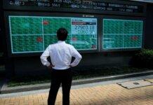 FOTO FILE: Seorang pria mengamati papan elektrik yang menunjukkan indeks Nikkei di luar broker di distrik bisnis Tokyo, Jepang, 21 Juni 2021. (REUTERS/Kim Kyung-Hoon via CNA)