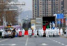 Orang-orang yang mengenakan masker dan pakaian desinfektan di pasar grosir makanan laut Huanan di Wuhan, China, pada Maret 2020. WHO telah membentuk tim ahli untuk menghasilkan kerangka kerja global baru untuk studi patogen yang muncul dari potensi pandemi, serta asal-usul Covid. (Foto: China News Service/Visual China Group via Getty Images via Guardian)