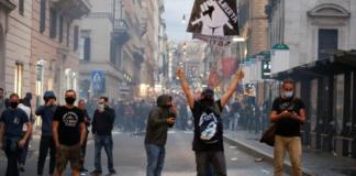 """Seorang demonstran memegang spanduk bertuliskan """"Liberta"""" atau 'Kebebasan' selama protes terhadap 'pintu hijau' di Roma, Italia [Remo Casilli/Reuters via Al Jazeera]"""