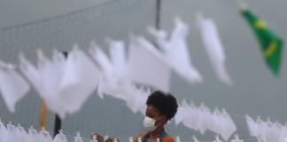 Seorang anggota LSM Rio de Paz meletakkan sapu tangan putih yang melambangkan perpisahan, untuk memberi penghormatan kepada 600.000 kematian akibat penyakit virus corona (Covid-19) di Brasil [Pilar Olivares/Reuters via Al Jazeera]